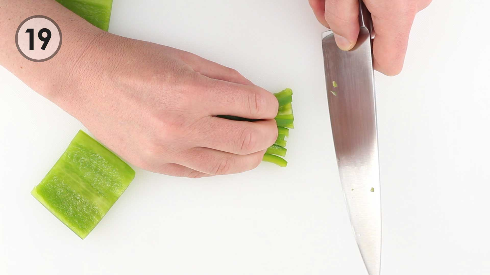 Step 19. Guide hand with fingers curled back over top of bell pepper julienne. Chef's knife being held with safe grip.